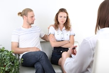 Young couple with problem in therapy session on reception for family psychologist